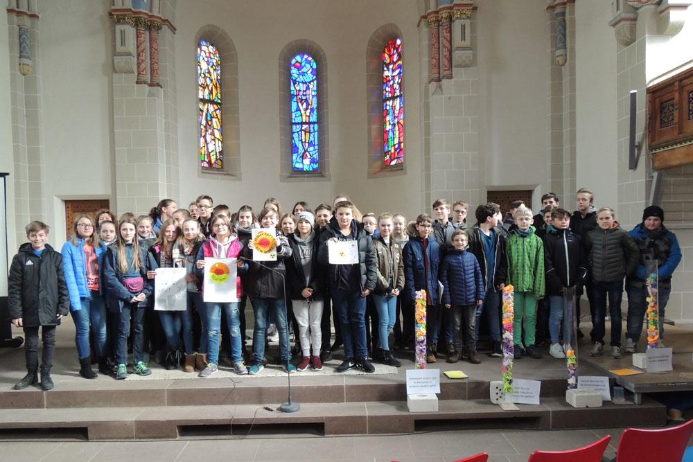 礼拝に参加した生徒たち。「原子力? おことわり」の自作ポスターを掲げる子どもも。