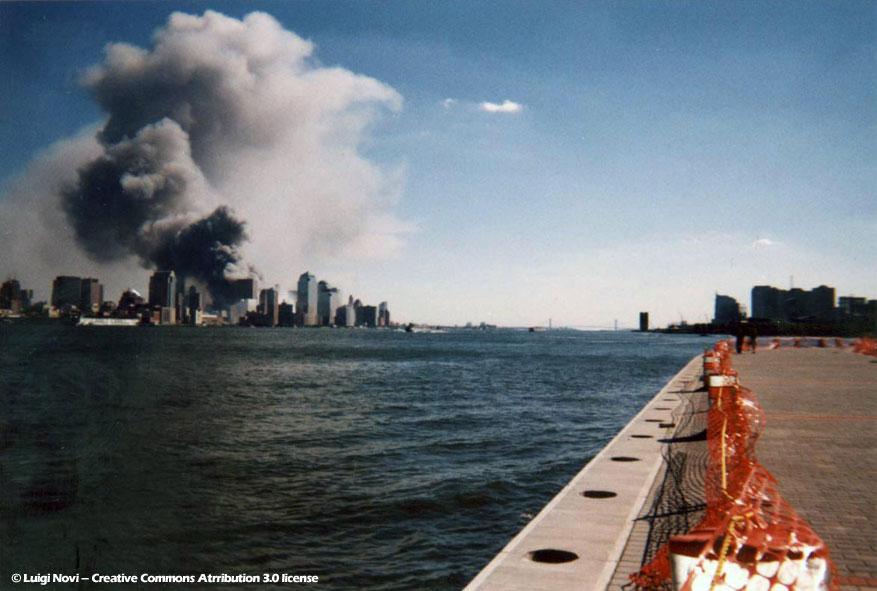 2001年9月11日、ボーイング767機が突っ込むというテロにより、二つのビルのそれぞれが、黒煙をあげるNYマンハッタンの貿易センタービル© Luigi Novi – Creative Commons Atrribution 3.0 license